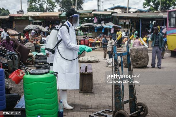 A staff member of Kenya's Ministry of Health sprays disinfectant on a pushcart to curb the spread of the COVID19 coronavirus at the Gikomba Market in...