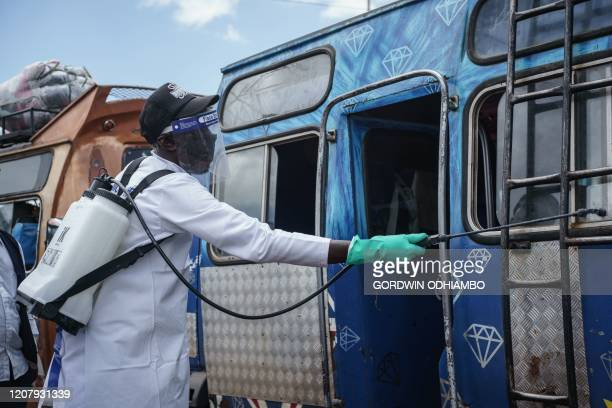 A staff member of Kenya's Ministry of Health sprays disinfectant on a minibus to curb the spread of the COVID19 coronavirus at the Gikomba Market in...