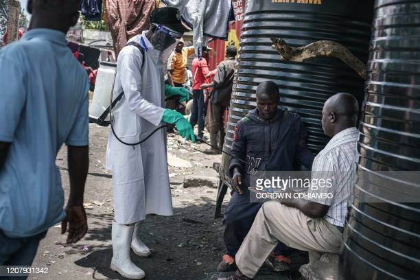 A staff member of Kenya's Ministry of Health sprays disinfectant on a game board to curb the spread of the COVID19 coronavirus at the Gikomba Market...