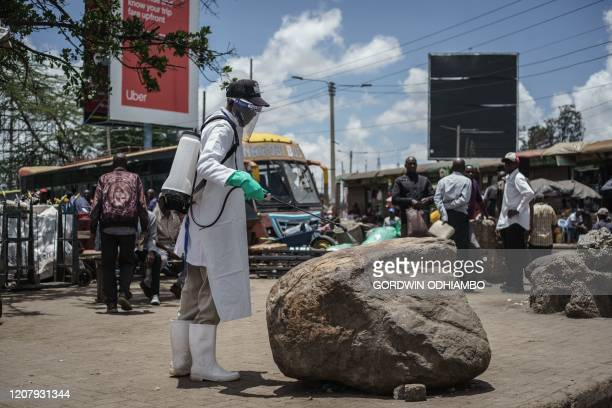 A staff member of Kenya's Ministry of Health sprays disinfectant on a rock which people sit on to curb the spread of the COVID19 coronavirus at the...
