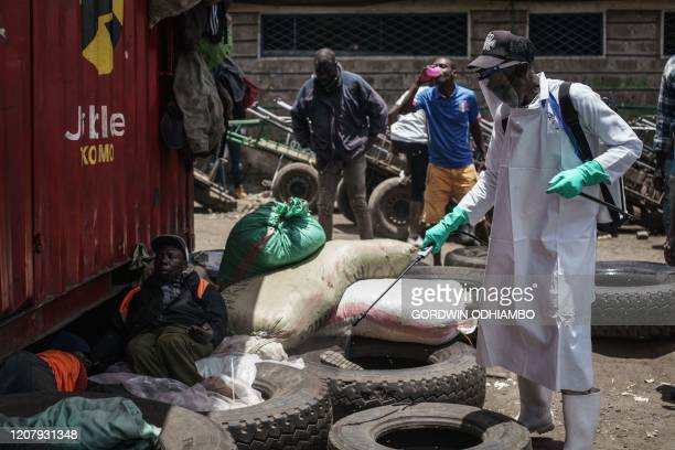 A staff member of Kenya's Ministry of Health sprays disinfectant to curb the spread of the COVID19 coronavirus at the Gikomba Market in Nairobi Kenya...