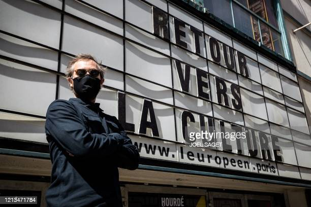 A staff member of L'Europeen theatre wearing a protective mask poses in front of the entrance next to the inscription reading Retour vers la culture...