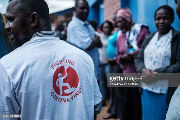 """Staff member of local NGO Shining Hope for Communities wears T-shirt that reads """"fighting corona virus"""" as the NGO installs hand washing stations at..."""