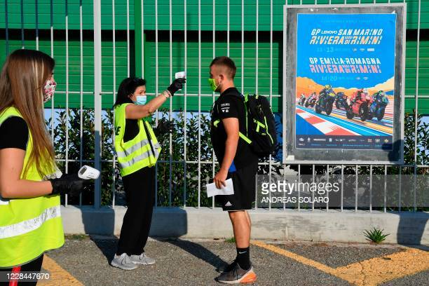Staff member of Misano Circuit checks the body temperature of a visitor as a preventive measure against the spread of the Covid-19 coronavirus, at...