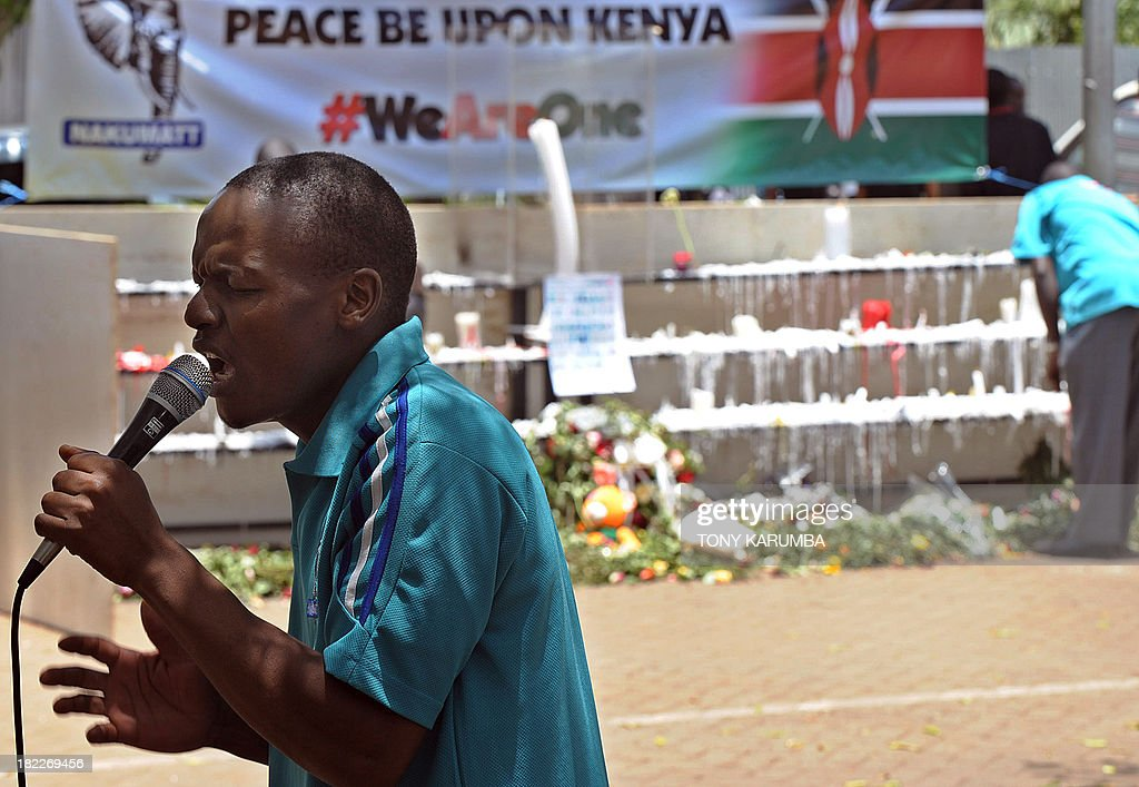 A staff member of Nakumatt supermarkets, who survived the four-day siege by Somali jihadists earlier in the week, prays on September 29, 2013 for the victims with fellow Nakumatt survivors outside the Westgate mall. Pressure mounted on the Kenyan authorities a week after the Nairobi mall carnage amid questions over the fate of the missing and accusations on September 28, 2013 that top brass failed to heed security warnings. President Uhuru Kenyatta has vowed not to bow to the Shebab group that claimed the Westgate mall bloodbath and threatened more attacks if Kenya failed to pull its troops out of Somalia. AFP PHOTO/Tony KARUMBA