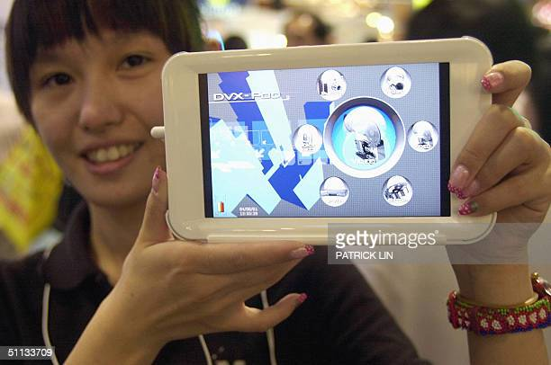 A staff member of Taiwan's MobiNote Technology Corp displays what she says is the world's first seveninch portable video player the DVXPOD 7010 at...
