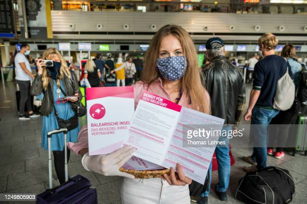 Staff member of the Balearic Islands Tourist Office holts a fakt sheeet for the tourists waiting to check in for a TUIfly flight to Mallorca at...