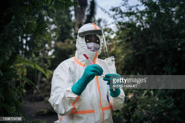Staff member of the Congolese Ministry of Health prepares the sampling equipment to perform a COVID-19 test at a private residence in Goma,...