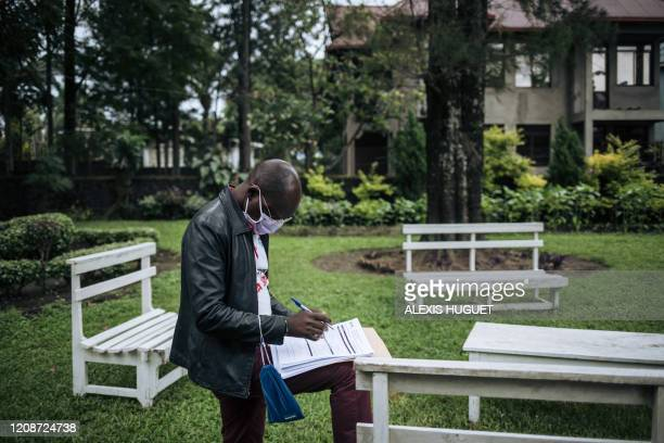 Staff member of the Congolese Ministry of Health records personal information after performing a COVID-19 test at a private residence in Goma,...