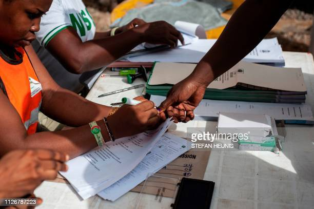 A staff member of the Independent National Electoral Commission marks the thumb of a voter at a polling unit in Lagos on February 23 2019 Nigerians...
