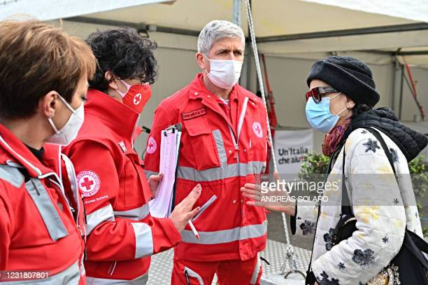 Staff member of the Italian Red Cross inform a woman at the entrance of a make-shift vaccination centre outside Rome's Termini train station in Rome...