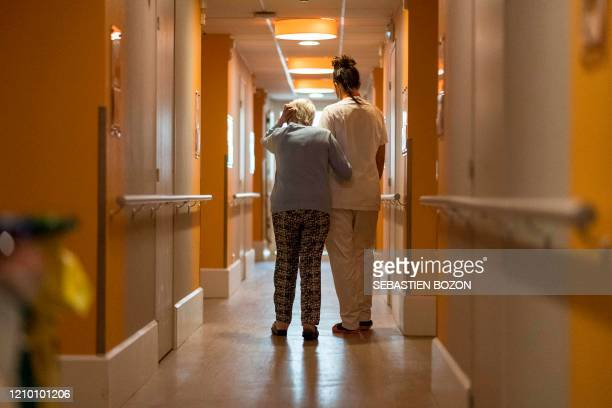 A staff member of the Korian Vill'Alize EHPAD in Thises eastern France helps a resident to walk on the corridor of the building on April 16 2020...