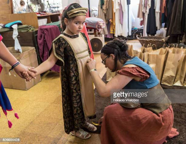 A staff member of the official wardrobe helps a little girl into a princess dress during the 21st edition of the Medieval Journey dedicated to the...