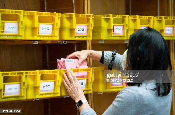 Staff member of the statistic office sorts postal voting envelopes by the numbers of the electoral districts on March 2, 2021 in Stuttgart, southern...