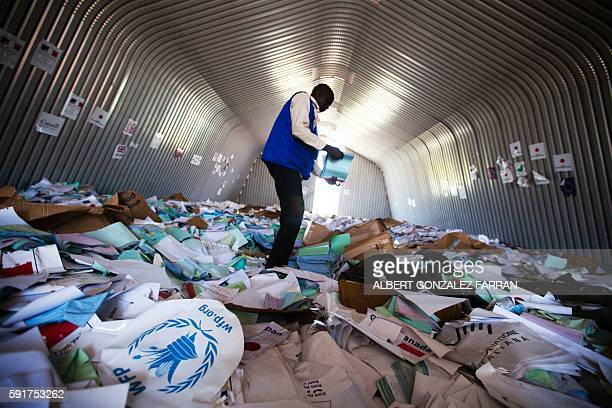 Staff member of the World Food Program examines on August 18, 2016 the remains of the logistic base of the United Nations organisation in the Jebel...