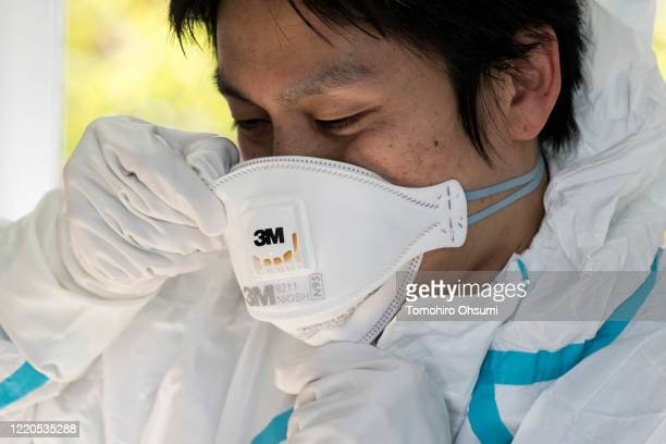 A staff member of the Yokosuka Medical Association wears a N95 mask before a demonstration collecting a swab sample for a polymerase chain reaction...
