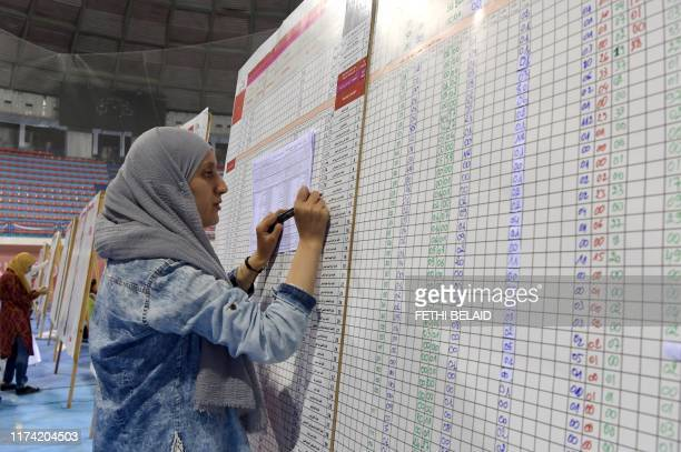 A staff member of Tunisia's Independent Higher Authority for Elections sorts through result lists of the legislatifs vote at a sorting station in the...