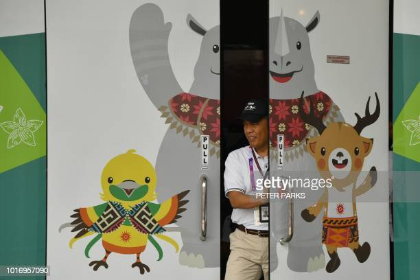 A staff member opens a door decorated with images of the official mascots of the 2018 Asian Games in Jakarta on August 15 2018