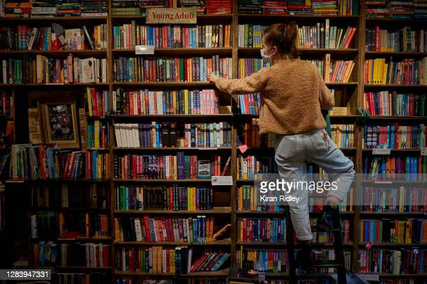 Staff member picks out a book for an order inside Shakespeare and Company Bookshop, which has appealed to its customers for help as France enters a...