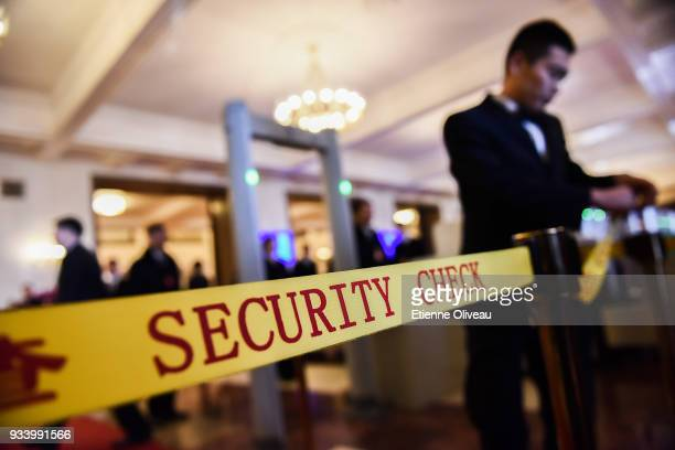 A staff member places a security check line at the entrance of the Great Hall of the People before the seventh plenary session of the 13th National...