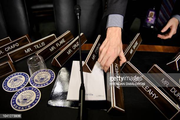 TOPSHOT A staff member places name plates as the Senate Judiciary Committee's room on Capitol Hill September 26 2018 in Washington DC during...