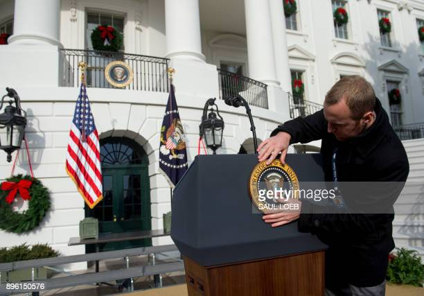 A staff member places the Presidential Seal on the podium prior to US President Donald Trump speaking about the passage of tax reform legislation on...