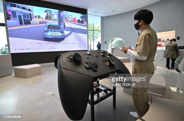 Staff member plays a game in front of an oversized mock-up of Microsoft's Xbox controller at a flagship store of SK Telecom in Seoul on November 10,...