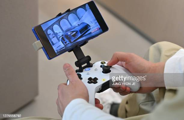 Staff member plays a game using Microsoft's Xbox controller at a flagship store of SK Telecom in Seoul on November 10, 2020.