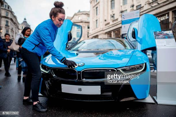 A BMW staff member poses cleaning the bonnet of a BMW i8 plugin hybrid sports car during the Regent Street Motor Show in London on November 4 2017 A...