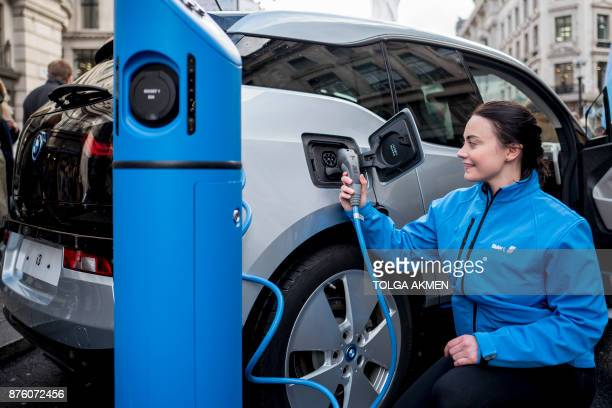 A BMW staff member poses for a photograph as she connects a BMW i3 electric vehicle to a charging point during Regent Street Motor Show on November 4...