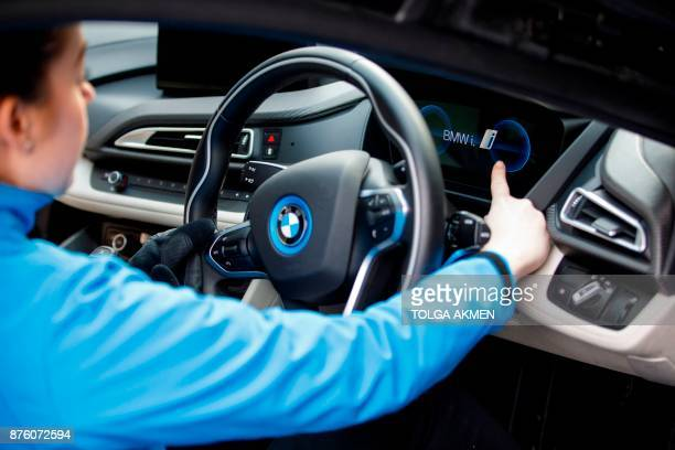A BMW staff member poses for a photograph in a BMW i8 plugin hybrid sports car during the Regent Street Motor Show in London on November 4 2017 A...
