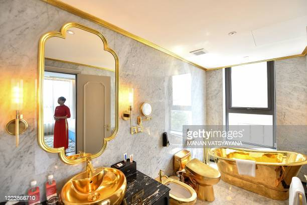 A staff member poses for a photograph inside the 1000 USD per night executive two bedroom suite of the newlyinaugurated Dolce Hanoi Golden Lake hotel...