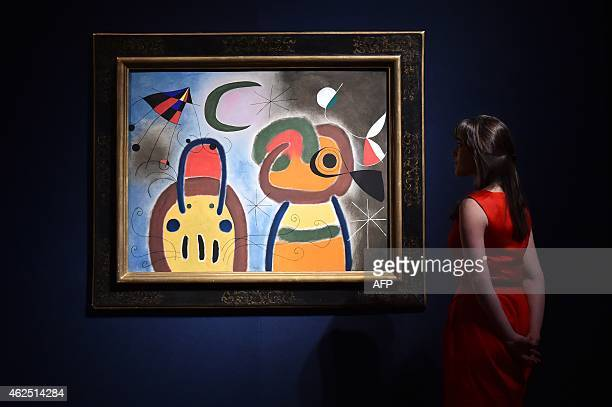 A staff member poses for pictures next to a painting by Joan Miro entitled L'Oiseau au plumage deploye vole vers l'arbre argente which is estimatd at...