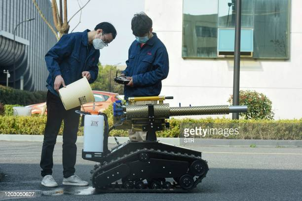 A staff member pours disinfectant into a tank on a robot as they disinfect at the Robot Town in Hangzhou in China's eastern Zhejiang province on...