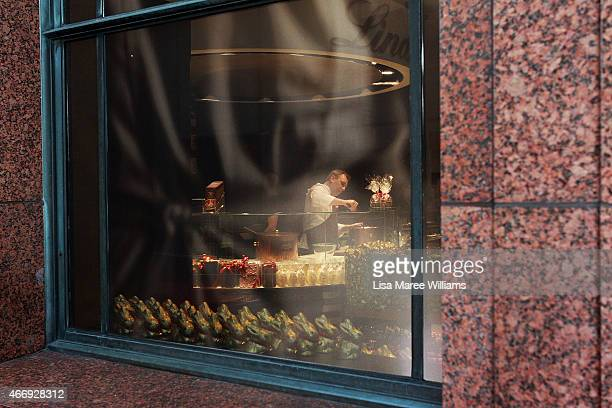 A staff member prepares chocolate as seen through the windows of the Lindt Cafe in Martin Place on March 20 2015 in Sydney Australia The cafe...