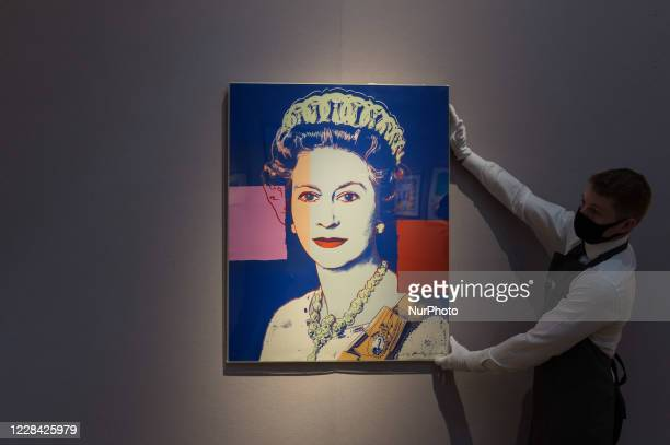 Editorial use only) A staff member presents 'Queen Elizabeth II' from: Reigning Queens screenprint in colours with diamond dust by Andy Warhol during...