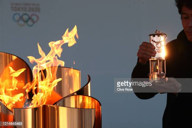 Staff preserves the Olympic flame to the lantern during the 'Flame of Recovery' special exhibition at Aquamarine Park a day after the postponement of...