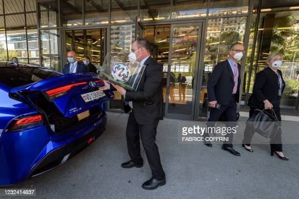 Staff member puts a mounted football of the EURO2020 tournament into the boot of the car of International Olympic Committee president as he leaves an...