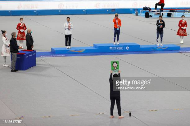 Staff member raises cue card to guide athletes wearing and taking off facial masks during the Women's 3000m medal ceremony on day one of the Speed...