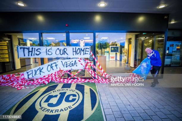 Staff member removes banners to protest against Roda JC's football club owner Mexican Mauricio Garcia de la Vega at the main entrance of Roda JC's...