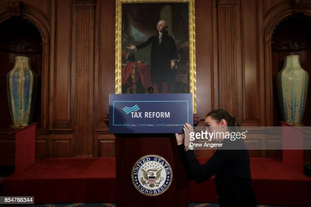 A staff member sets the stage before a news conference to where Republican lawmakers will announce their plans for tax reform September 27 2017 in...