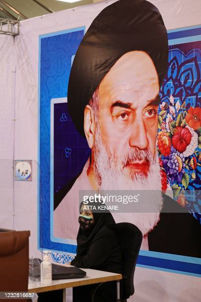 Staff member sits under a portrait of the late Iranian revolutionary leader Ayatollah Ruhollah Khomeini, while registering candidates for Iran's...