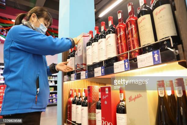 Staff member sorts Australian wine in an area selling imported wine in a bonded warehouse in Nantong, in eastern China's Jiangsu province on November...