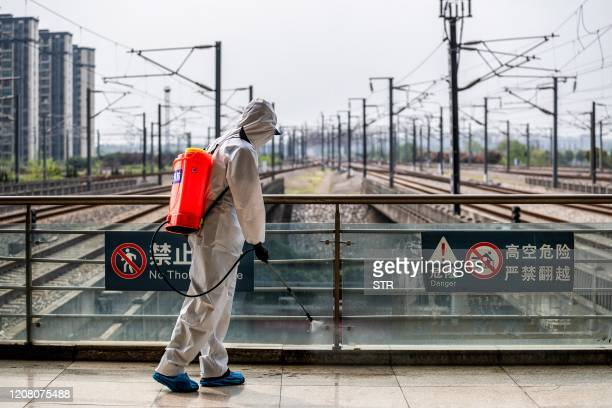 Staff member sprays disinfectant at Wuhan Railway Station in Wuhan in China's central Hubei province on March 24, 2020. - China announced on March 24...