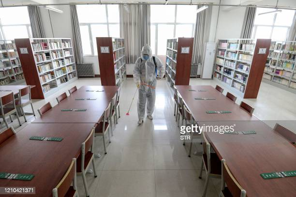 Staff member sprays disinfectant in the library of a school as it prepares to reopen after the term opening was delayed due to the COVID-19...