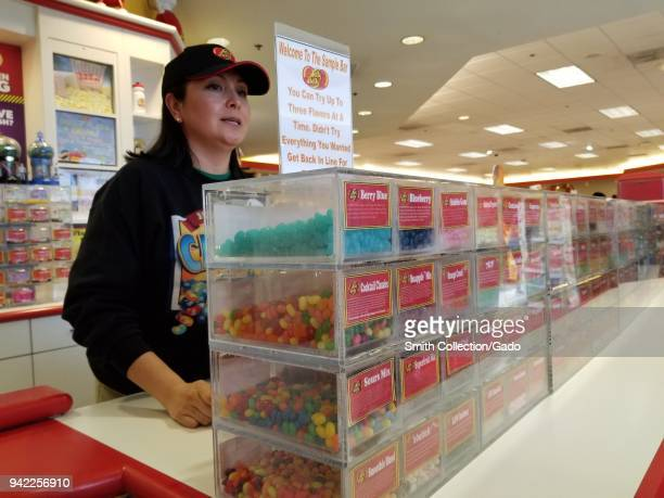 A staff member stands behind the Tasting Bar at the Jelly Belly jelly bean candy factory in Fairfield California and offers free samples of every...