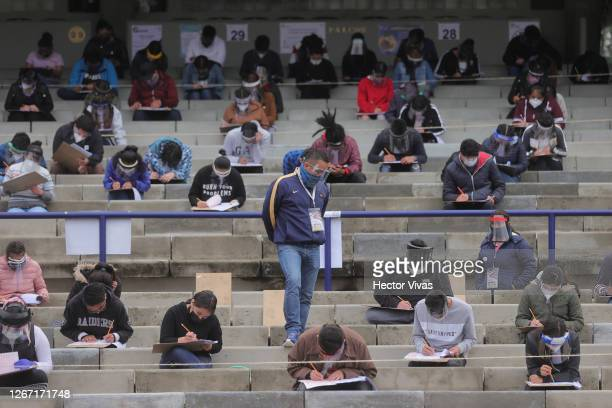 Staff member stands guard among students who take their UNAM admission exam while following the preventive measuress to avoid Covid-19 at Olimpico...