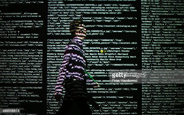 A staff member stands in a projection of live data feeds from Twitter Instagram and Transport for London by data visualisation studio Tekja at the...