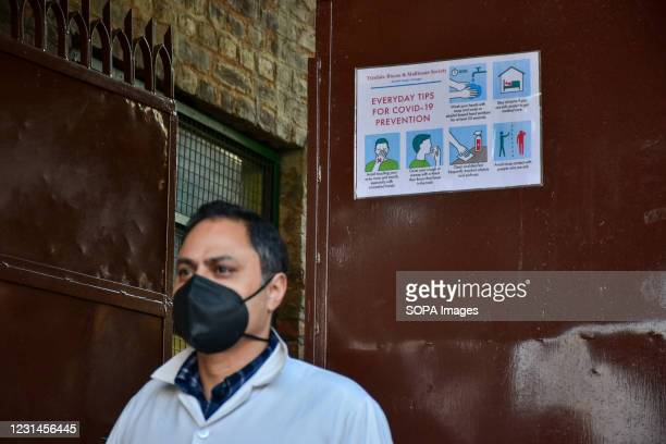 Staff member stands in front of the poster of Covid-19 precautions inside the school premises as the schools reopened after one year of break due to...