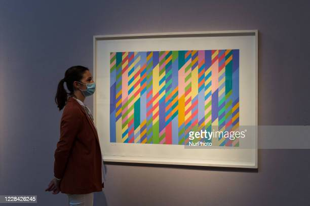 Editorial use only) A staff member stands next to 'June', screenprint in colours, 1992-2002, by Bridget Riley during a press preview at Christie's on...